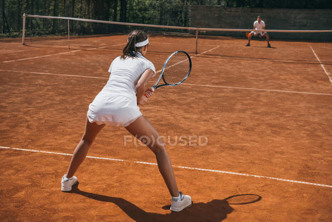 Молодая атлетичная женщина в спортивной одежде играет в теннис с мужчиной — стоковое фото