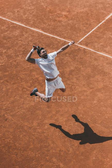 Висока кут зору молодих тенісист, роблячи хіт в стрибок — стокове фото