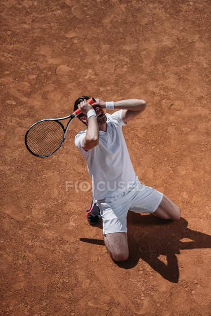 Hochwinkelaufnahme eines Mannes, der auf Knien steht und weint, nachdem er ein Tennismatch verloren hat — Stockfoto