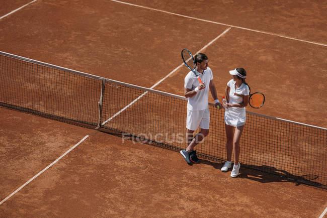 Vista de ángulo alto de joven guapo coqueteando con mujer en cancha de tenis - foto de stock