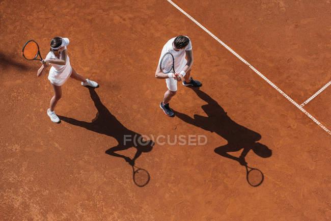 Blick aus der Vogelperspektive auf ein junges sportliches Paar, das als Team Tennis spielt — Stockfoto