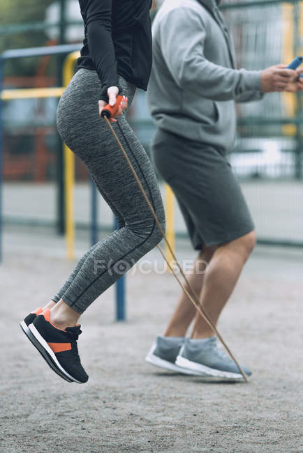 Cropped image of sportsman and sportswoman jumping ropes — Stock Photo