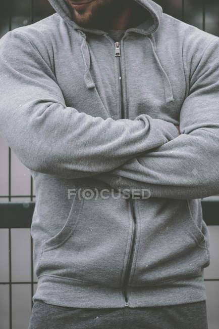 Immagine ritagliata di sportivo in piedi con le mani incrociate vicino alla recinzione al campo sportivo — Foto stock