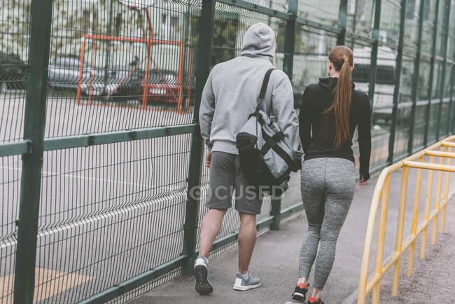 Blick von hinten auf sportliches Paar zu Fuß zum Sportplatz — Stockfoto