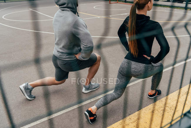 View through fence on sportsman and sportswoman doing lunge exercise — Stock Photo