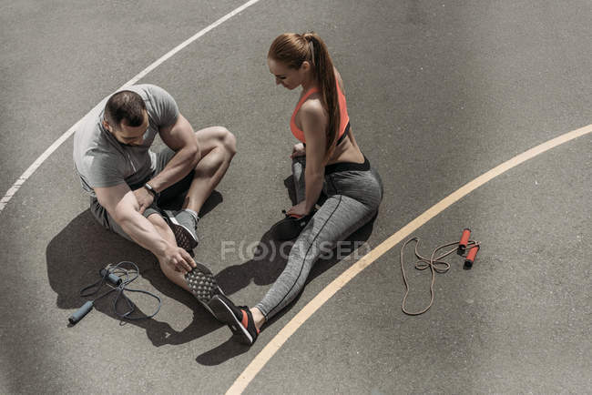 Overhead view of sportswoman and sportsman stretching at sports ground — Stock Photo