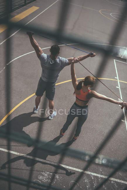 Blick durch Zaun von Mann und Frau beim Seilspringen — Stockfoto