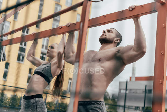 Sportsman and sportswoman pulling up at horizontal bar together — Stock Photo
