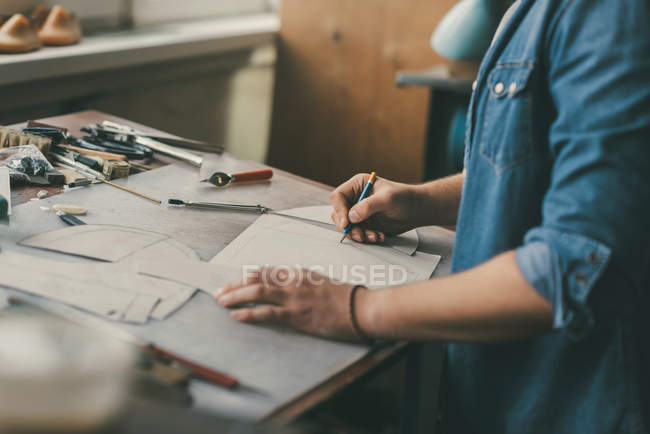 Partial view of cobbler in denim shirt drawing outline for shoes at workshop — Stock Photo