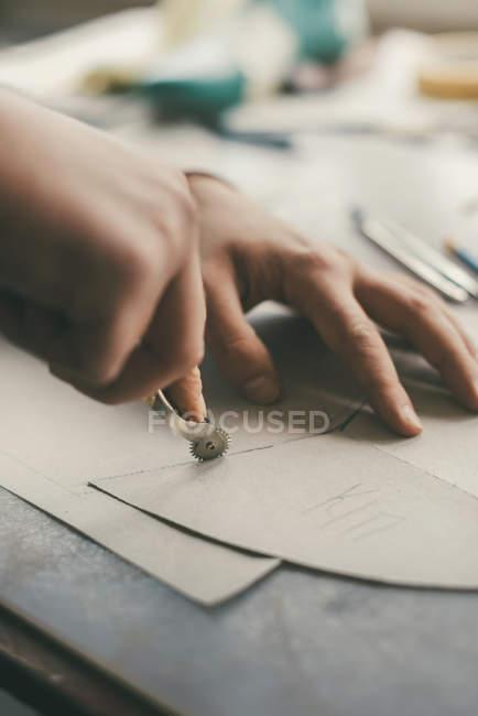Tiro recortado de artesãos rastreando folhas de couro para criar sapatos — Fotografia de Stock