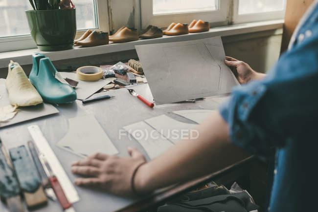 Recadrée tir de dessin esquisse de cordonnier pour chaussures à l'atelier — Photo de stock