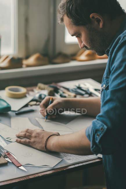 Couro de rastreamento de sapateiro de meia idade focado para sapatos na oficina — Fotografia de Stock