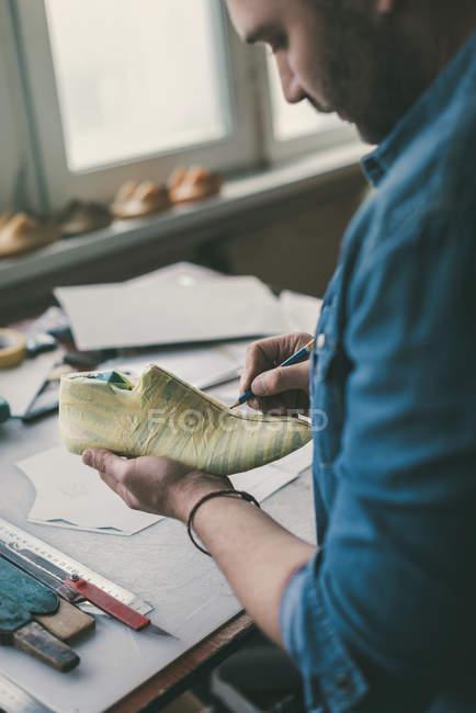 Tiro recortado del zapatero que trabaja con la muestra del pie - foto de stock