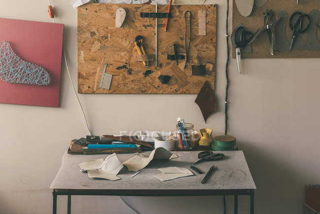 Table with leather samples and various tools with scissors at shoemaker workshop — Stock Photo