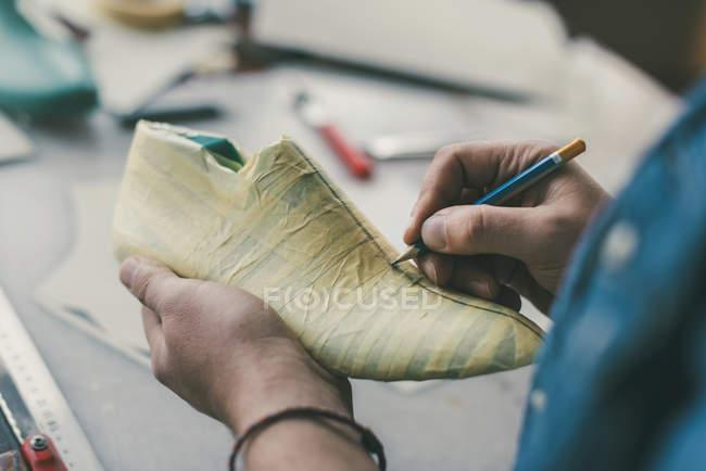 Обрезанный кадр сапожника, держащий карандаш и работающий с незаконченной обувной заготовкой — стоковое фото