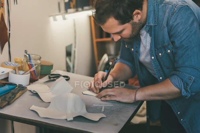 Jovem sapateiro rastreando couro para sapatos no local de trabalho — Fotografia de Stock