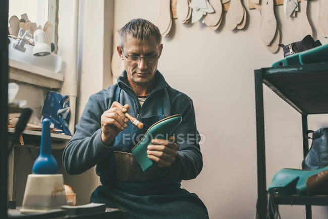 Mature shoemaker holding boot workpiece and working with sole at his traditional workshop — Stock Photo