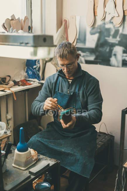 Sapateiro maduro segurando peça de inicialização e trabalhando com sola enquanto sentado em sua oficina tradicional — Fotografia de Stock
