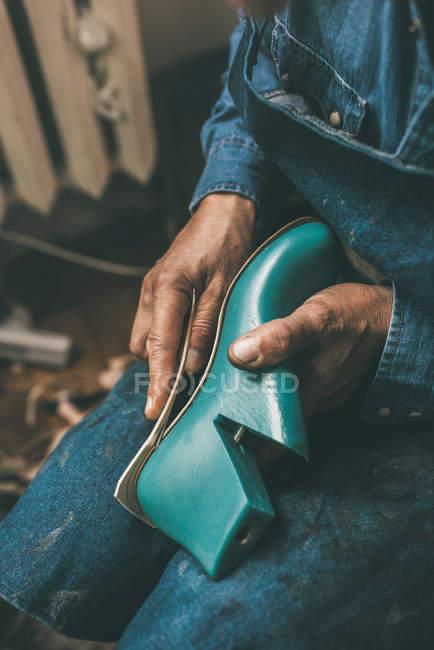 Tiro recortado de sapateiro segurando peça de trabalho de inicialização e contorno de sola de medição na oficina — Fotografia de Stock