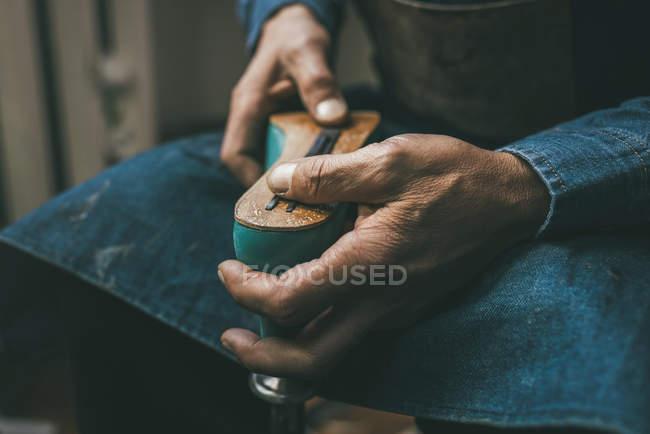 Visão parcial do sapateiro segurando peça de plástico de inicialização e trabalhando com contorno único — Fotografia de Stock