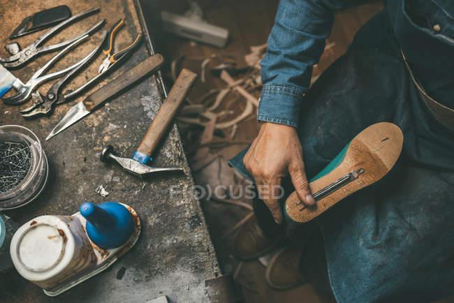 Tiro recortado de sapateiro segurando peça de trabalho de inicialização de plástico e trabalhando com contorno único — Fotografia de Stock