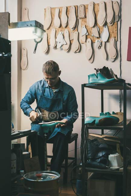 Sapateiro maduro trabalhando com peças de calçado na oficina — Fotografia de Stock