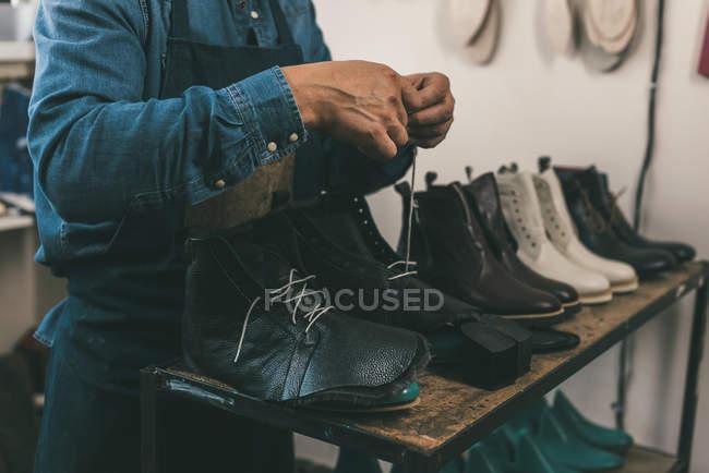 Tiro cortado de sapateiro amarrando botas de couro inacabados na oficina — Fotografia de Stock