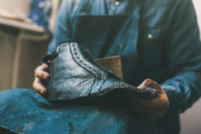 Cropped shot of cobbler holding unfinished leather shoe at workshop — Stock Photo