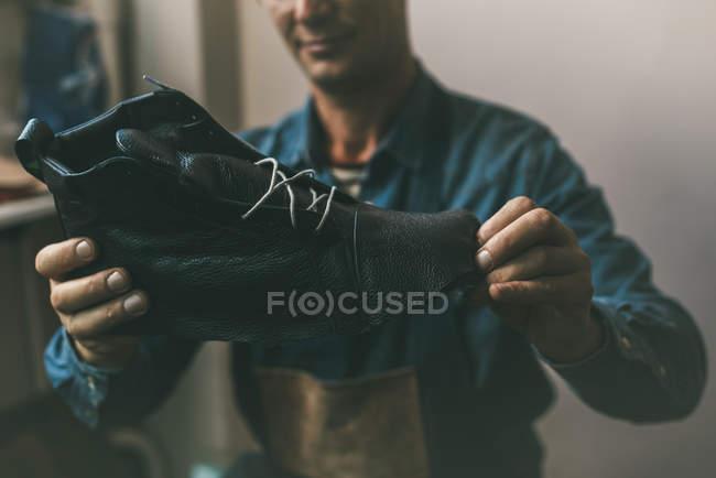 Close-up tiro de sapateiro olhando para a bota de couro inacabado — Fotografia de Stock