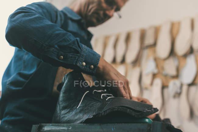Close-up tiro de sapateiro amarrando botas de couro inacabado — Fotografia de Stock