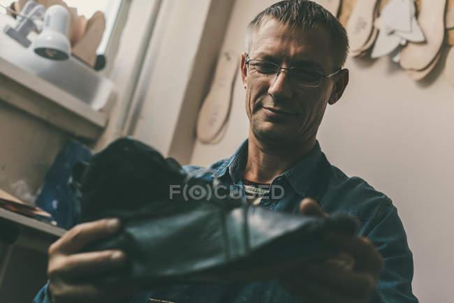 Foco seletivo de sorrir sapateiro maduro em óculos segurando sapato de couro na oficina — Fotografia de Stock
