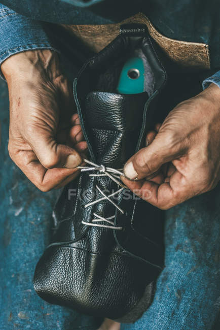 Tiro cortado de sapateiro amarrando botas de couro inacabado — Fotografia de Stock