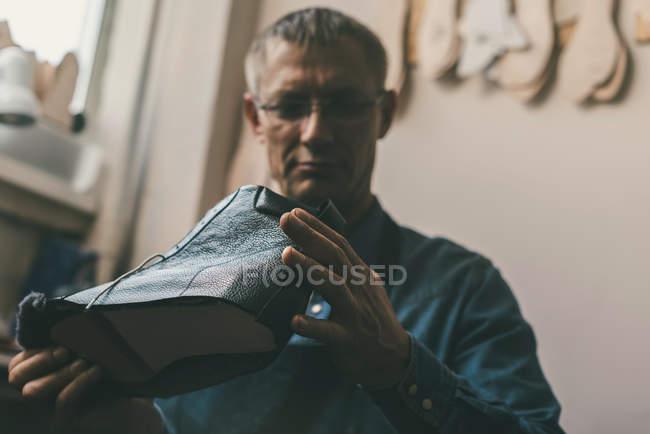 Sapateiro maduro olhando para bota de couro inacabado — Fotografia de Stock