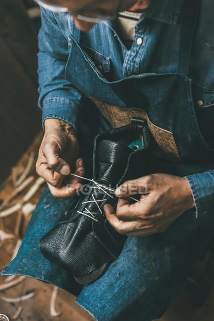 Sapateiro amarrando botas de couro inacabado — Fotografia de Stock