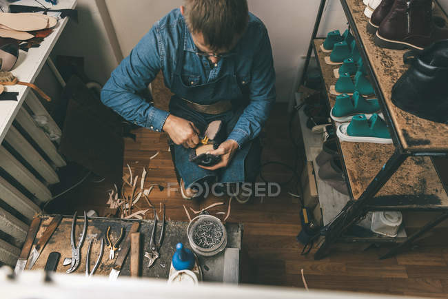Overhead view of mature shoemaker working with diy tools in workshop — Stock Photo