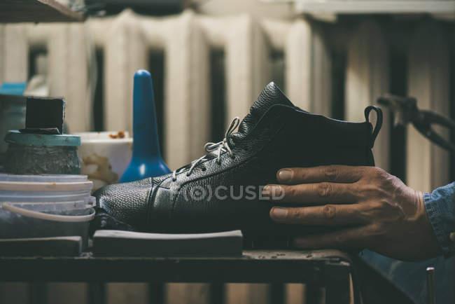 Close-up vista parcial de sapateiro segurando sapato de couro na oficina — Fotografia de Stock