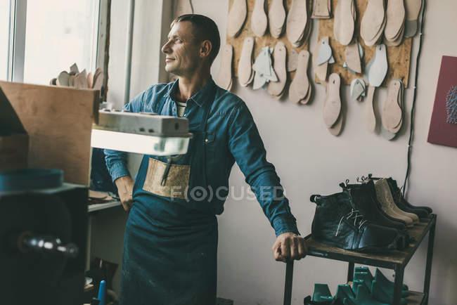 Вдумчивый сапожник в рабочей одежде и фартук в мастерской — стоковое фото