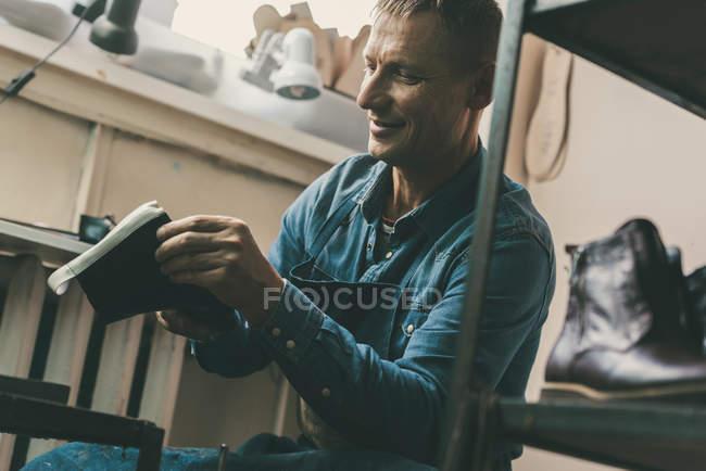 Sapateiro adulto sorridente trabalhando em par de sapatos na oficina — Fotografia de Stock