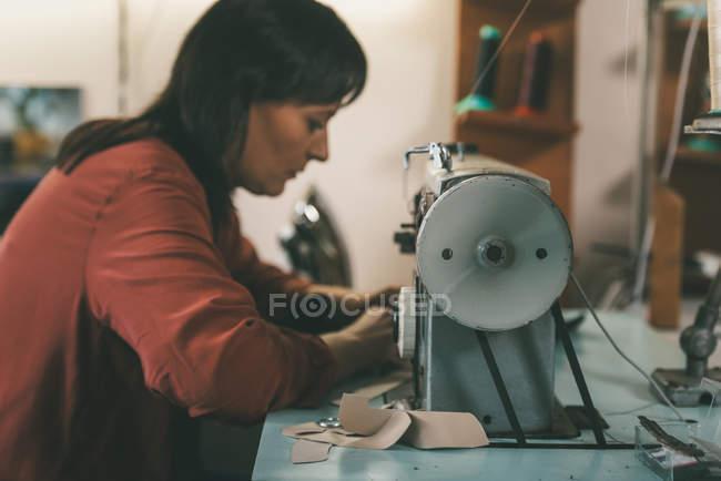 Vista lateral da costureira trabalhando com máquina de costura e couro na oficina sapateiro — Fotografia de Stock