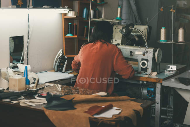 Rückansicht der Näherin bei der Arbeit mit Nähmaschine und Leder in der Schuhmacherwerkstatt — Stockfoto