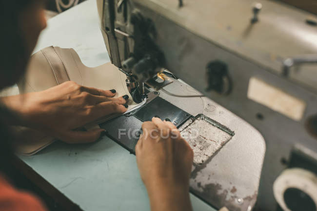 Close-up partial view of seamstress working with sewing machine and leather at shoemaker workshop — Stock Photo