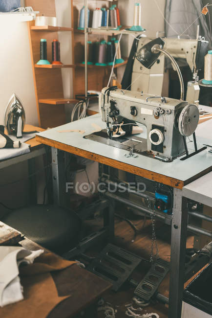 Workplace of seamstress at tailor shop with electrical industrial sewing machine — Stock Photo