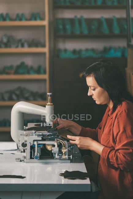 Vista lateral da costureira de meia idade trabalhando com máquina de costura e couro na oficina sapateiro — Fotografia de Stock