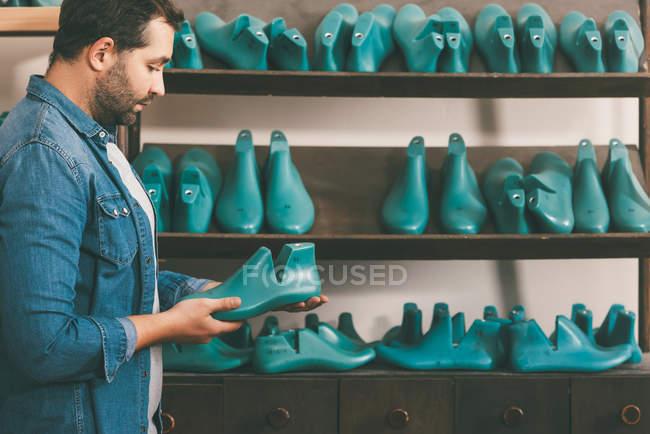 Vista lateral do sapateiro barbudo segurando peça de calçado na oficina — Fotografia de Stock