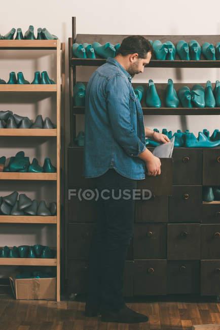 Vista laterale del calzolaio che tiene le carte mentre lavora con pezzi di calzature in officina — Foto stock
