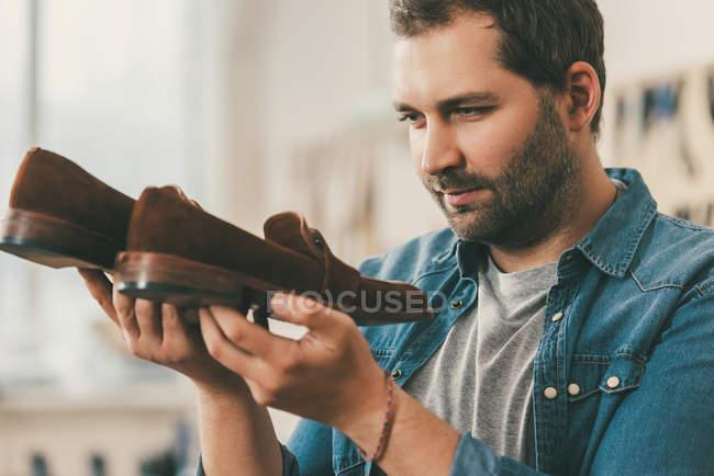 Sapateiro de meia idade barbudo segurando par de sapatos de couro — Fotografia de Stock