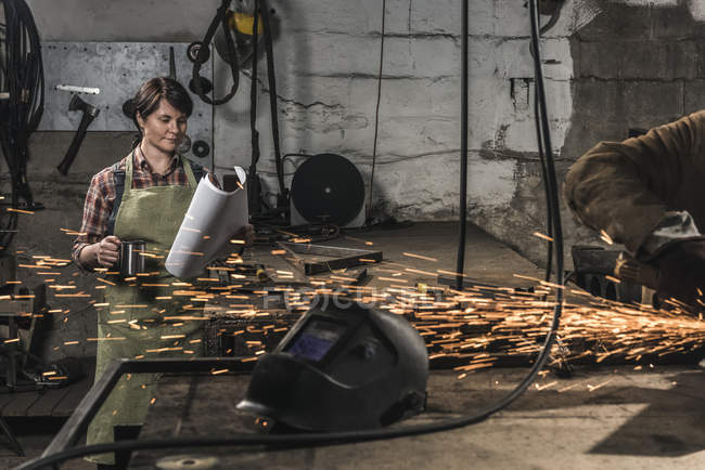 Welder with cup of hot drink reading papers while colleague working in workshop — Stock Photo