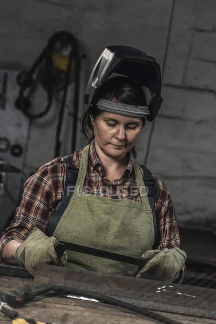 Portrait of female welder in protective helmet in workshop — Stock Photo