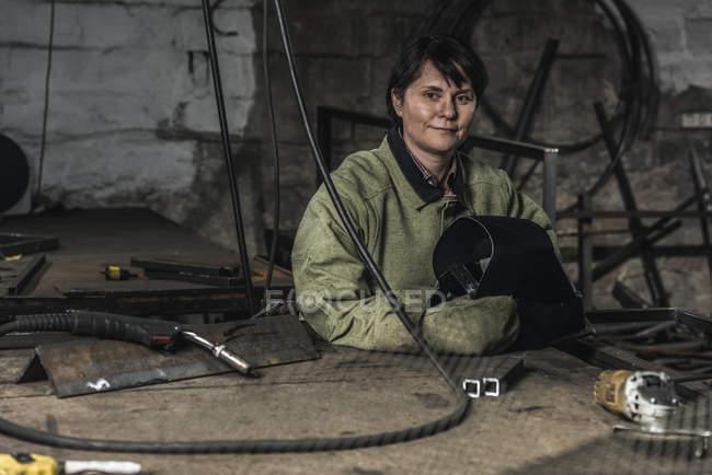 Portrait of smiling female welder with protective helmet in hands in workshop — Stock Photo