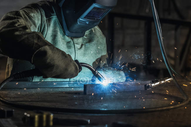 Manual worker in protective helmet with welding torch working in workshop — Stock Photo